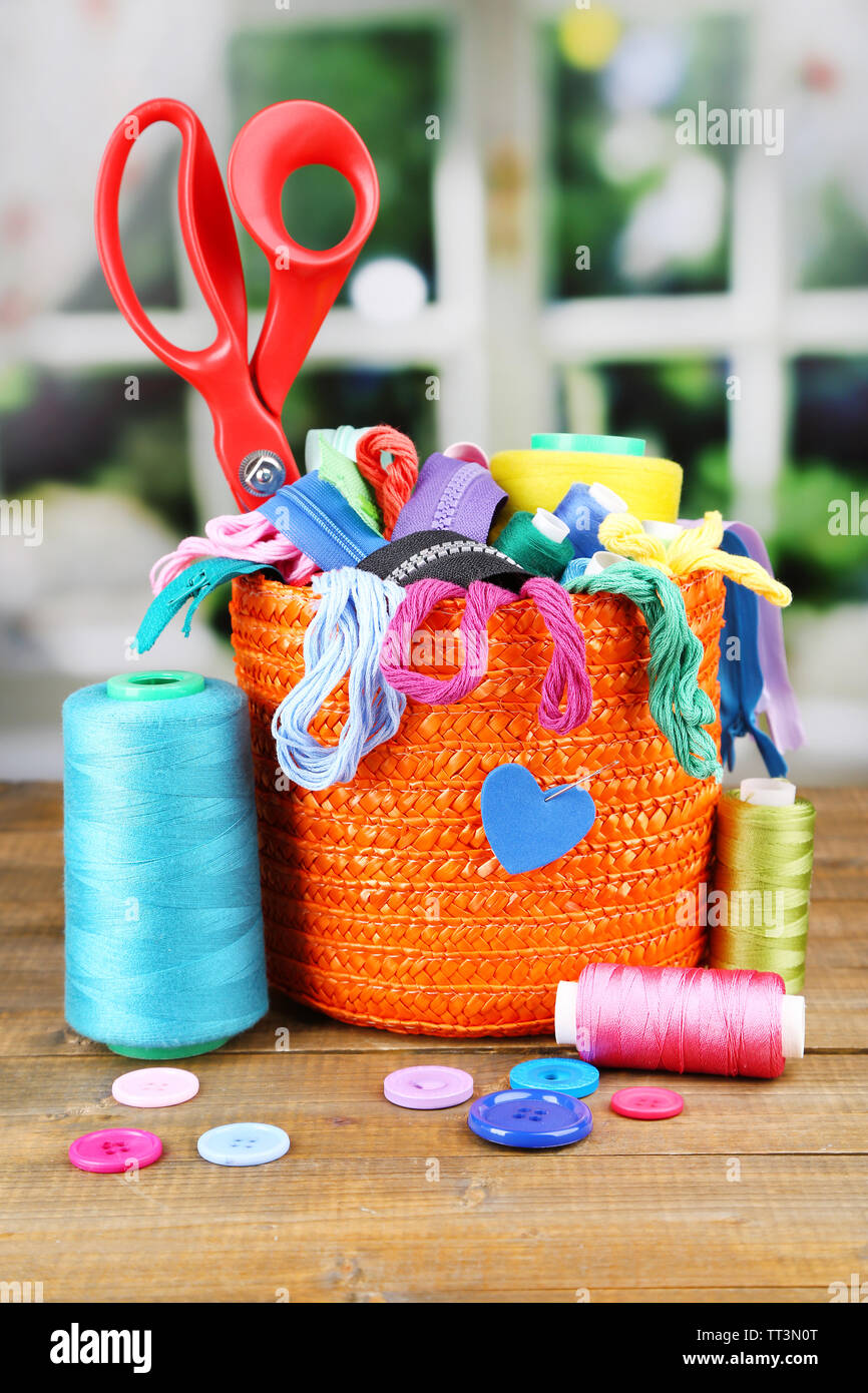 Round orange box full of multicoloured thread and everything necessary for sewing on a brown wooden table on window background - Stock Image