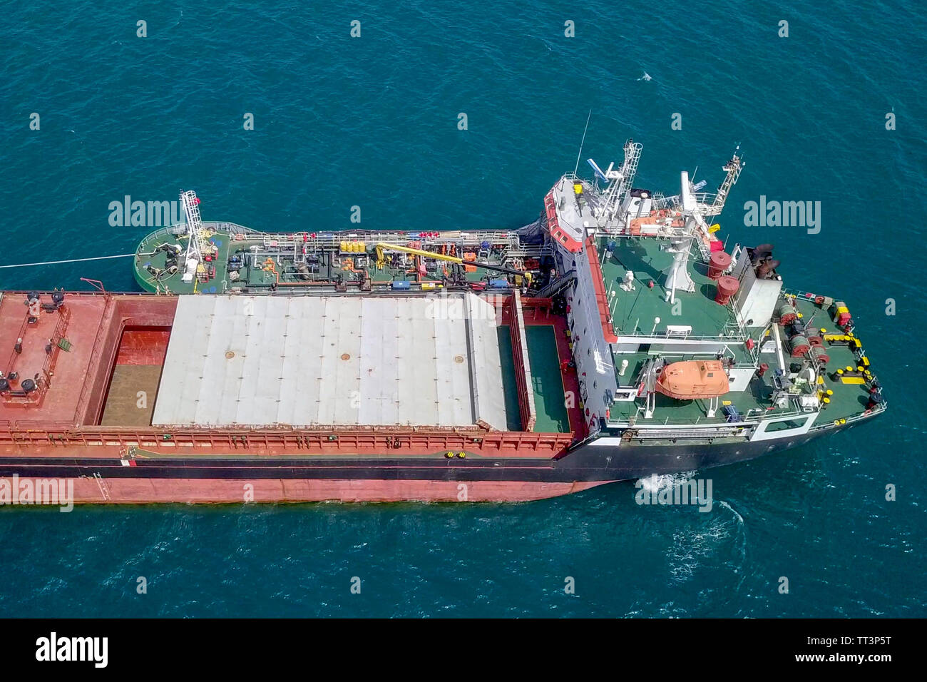 Refuelling at sea - Small Oil products ship fuelling a large Bulk carrier, aerial image. Stock Photo