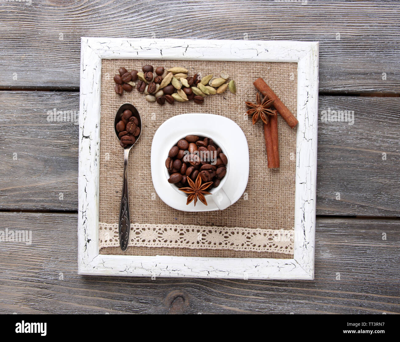 Wooden frame with white mug, coffee grains and spices on wooden background Stock Photo