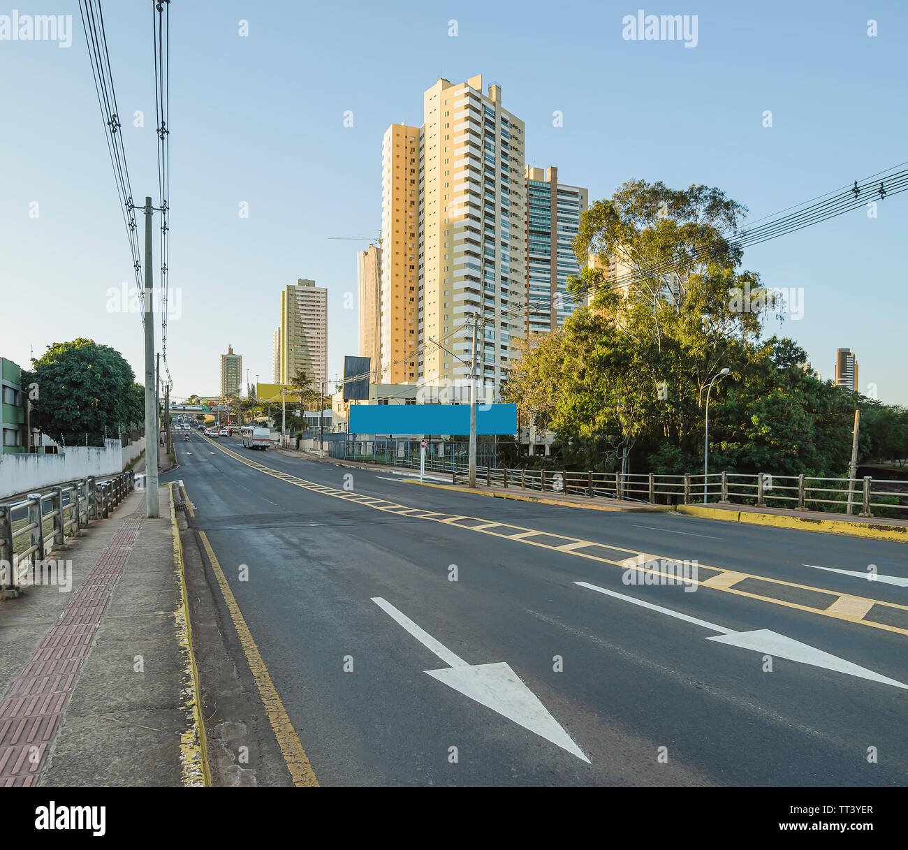 Brazilian large avenue with directional arrows on the street. Electric poles and few buildings on background. Ceara Avenue at the capital city, Campo Stock Photo