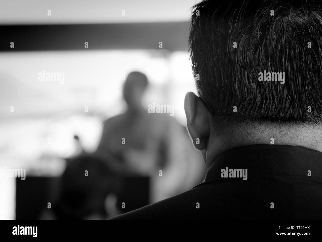 Back view of a man wearing a black dress, listening to the monk preaching at the funeral. Funeral in Thailand. Thai Buddhist funeral. Death - Stock Image
