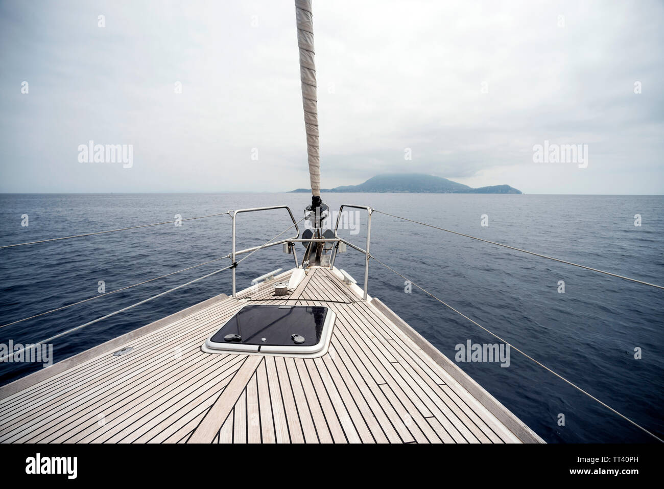 Bow of sailing yacht with land in sight - Stock Image