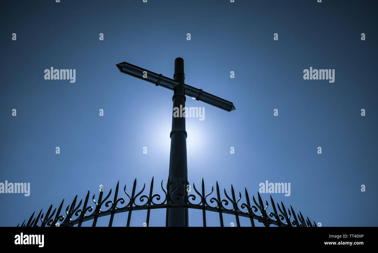 Stainless steel cross and fence on blue sky and sun light background. Crucifix of Jesus Christ. God light and forgiveness concept. Crosses, Christian - Stock Image