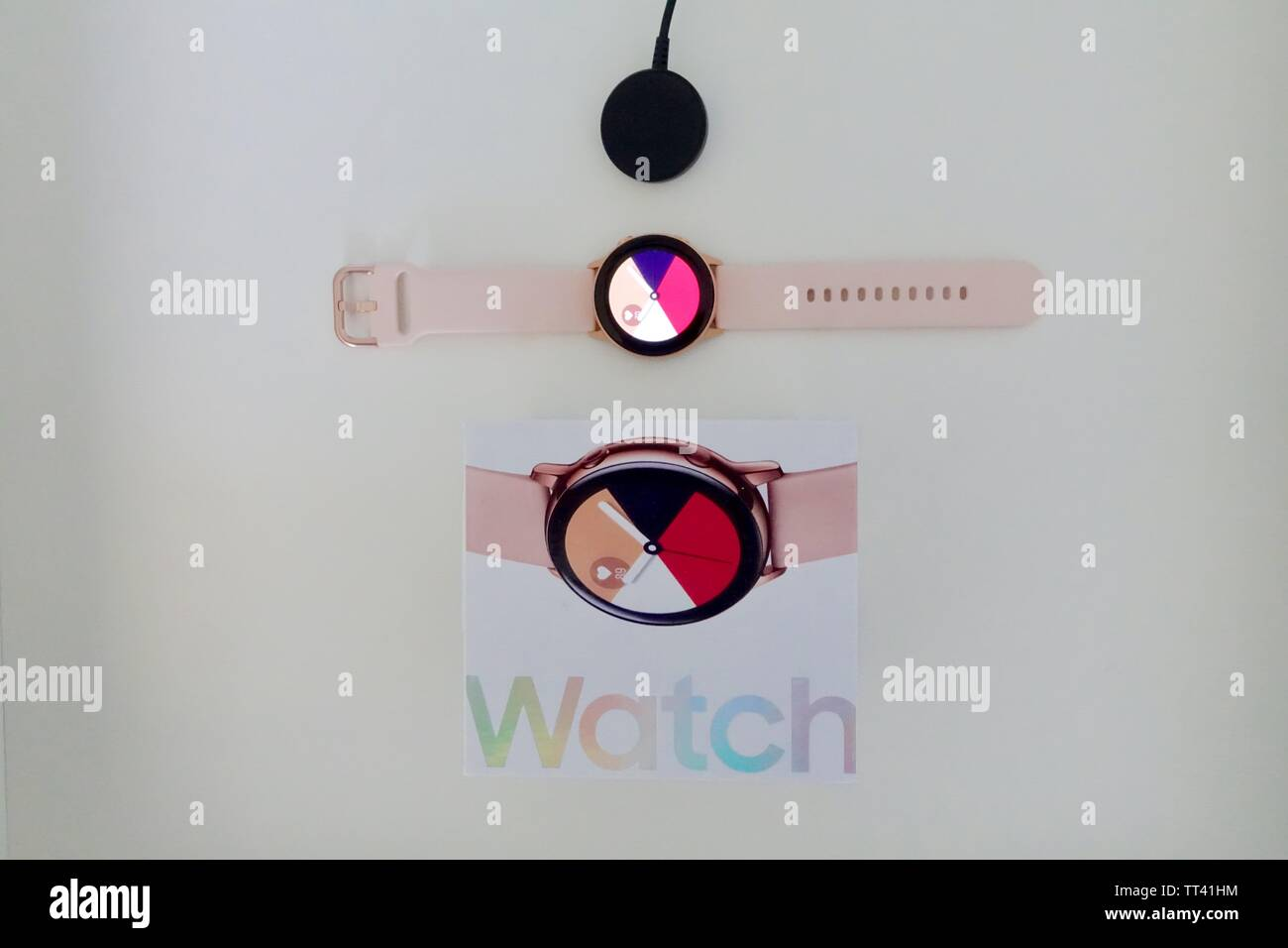 Orlando, FL/USA- 6/7/19: A rose gold Samsung Galaxy Active watch open with a standard watch face, box and charging disk. - Stock Image