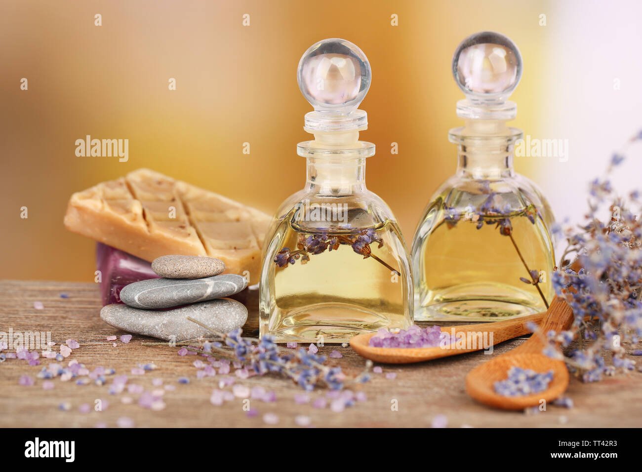 Spa still life with lavender oil and flowers on wooden table, on light background - Stock Image