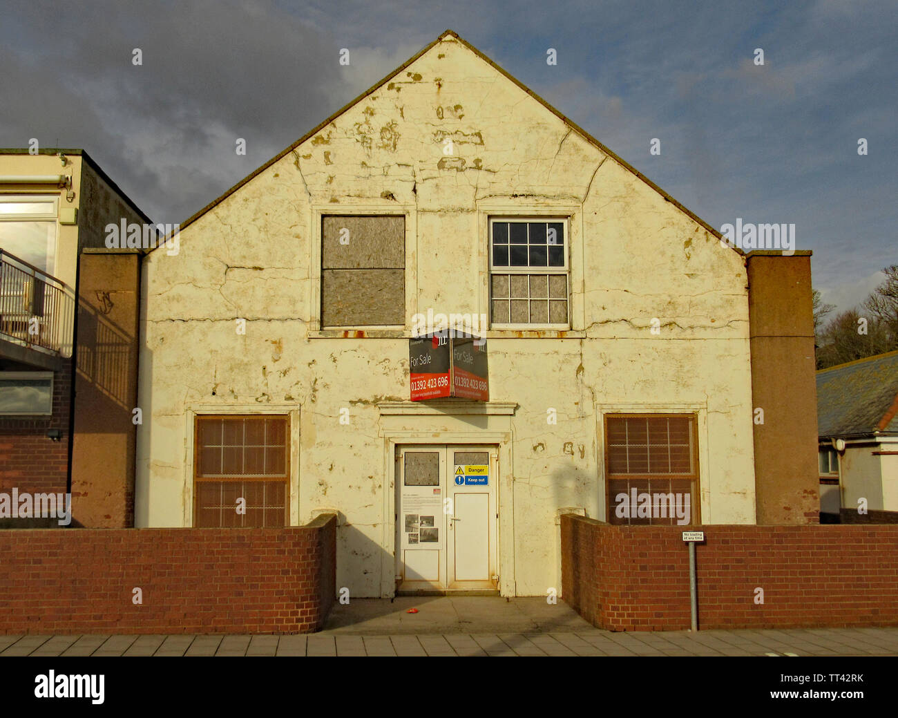 The drill hall at the eastern end of Sidmouth Esplanade. A building which has been deteriorating for many years. - Stock Image