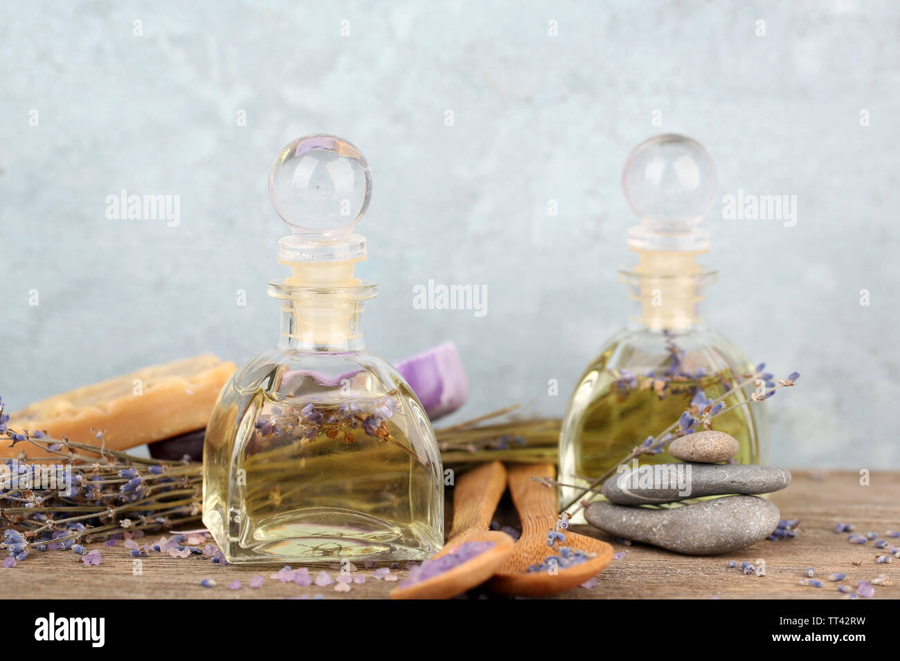 Spa still life with lavender oil and flowers on wooden table, on grey background - Stock Image
