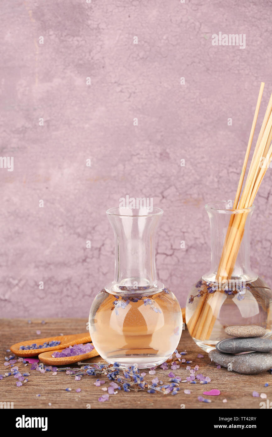 Spa still life with lavender oil and flowers on wooden table, on pink background - Stock Image