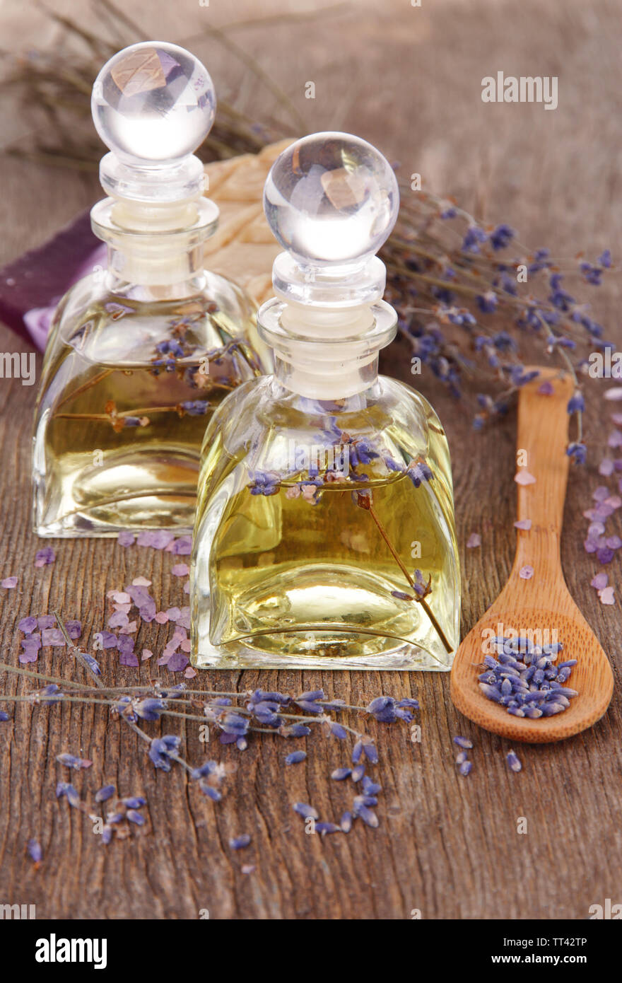 Spa still life with lavender oil and flowers on wooden table - Stock Image