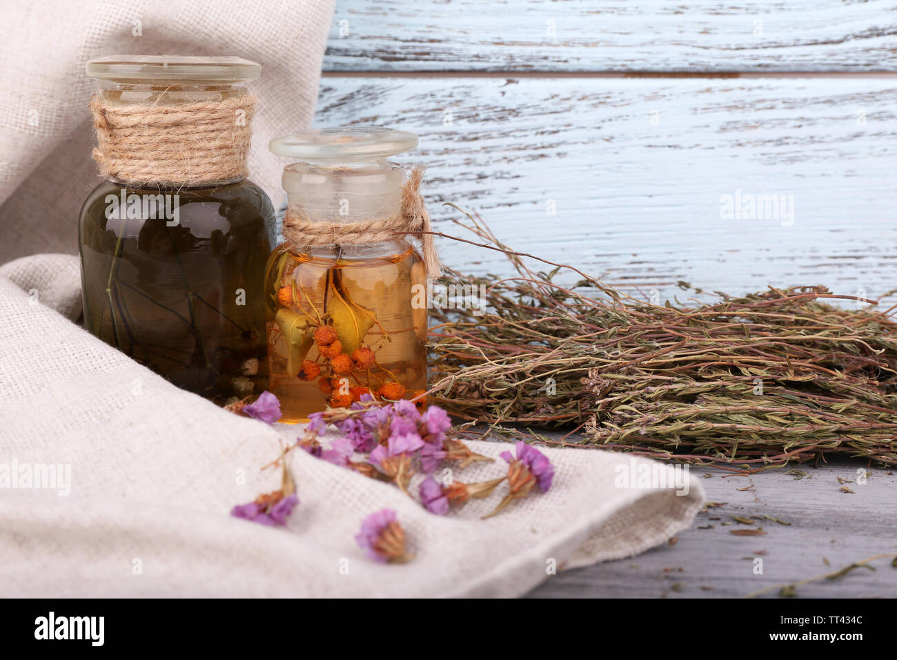 Bottles of herbal tincture and dried herbs on a napkin on wooden background in front of curtain - Stock Image