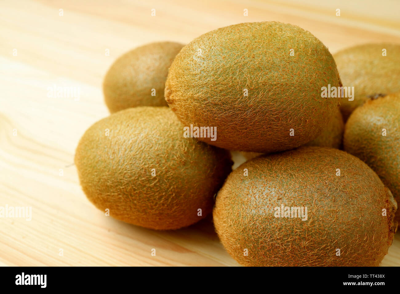 Closeup Heap of fresh kiwi fruits isolated on the wooden table - Stock Image