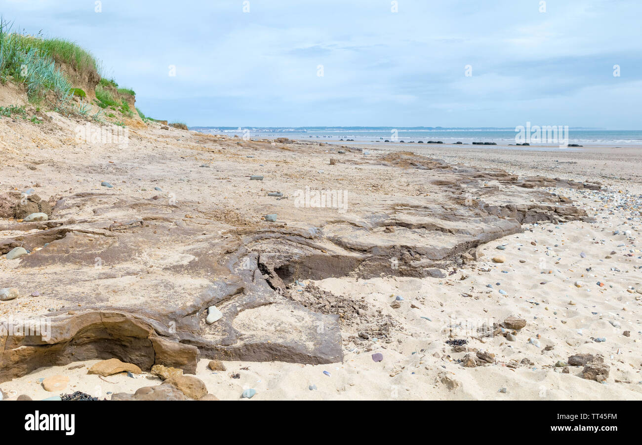 English shoreline along rocky coast and sandy beach on sunny morning in summer with view of sea under blue sky, Fraisthorpe, Yorkshire, UK. Stock Photo