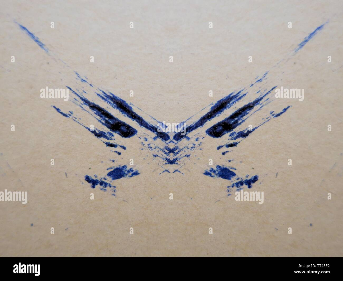 Blue ink smudge on beige paper, abstract. - Stock Image