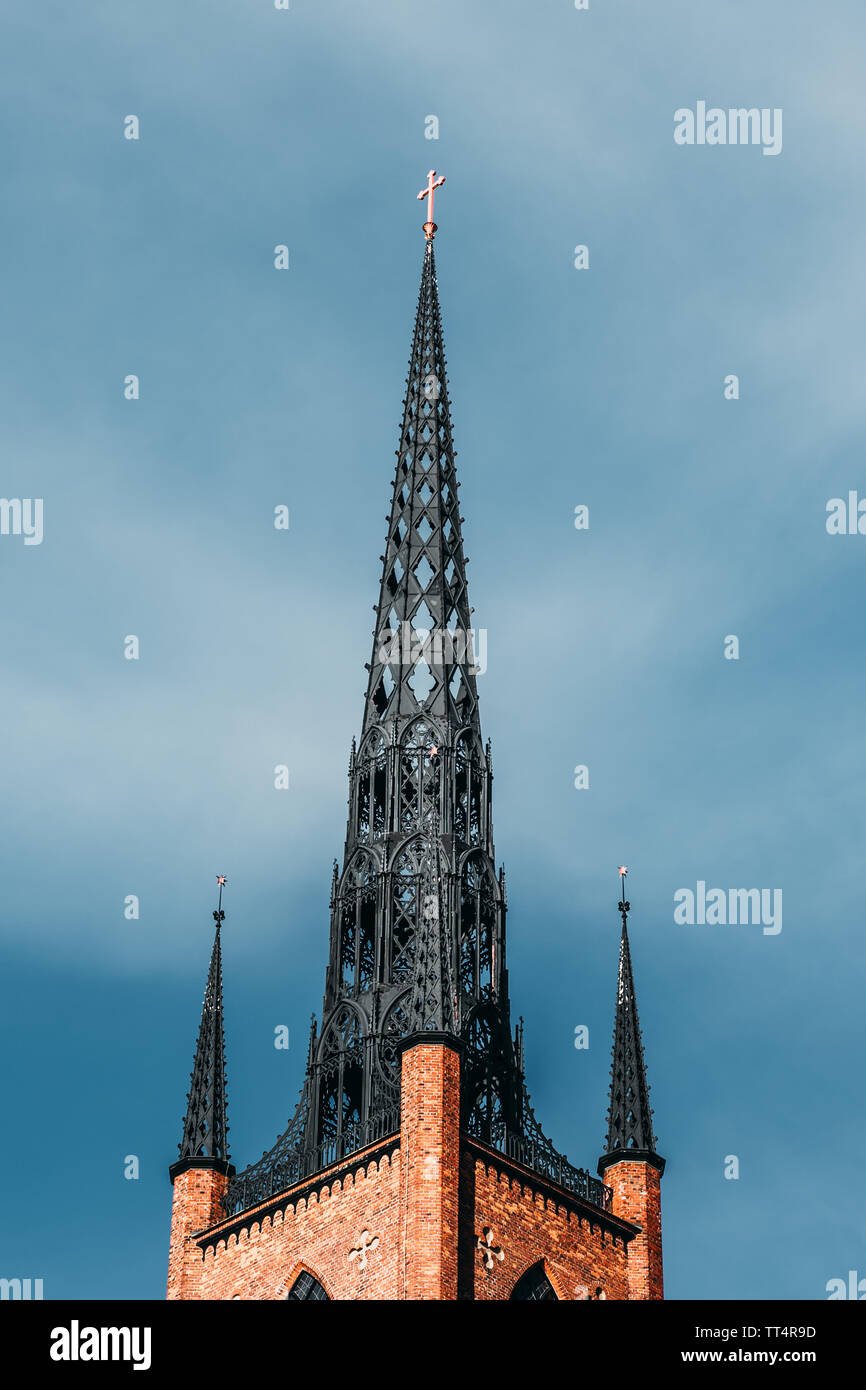 Old steel church tower with brick base with clear blue sky in the background, Stockholm Sweden - Stock Image