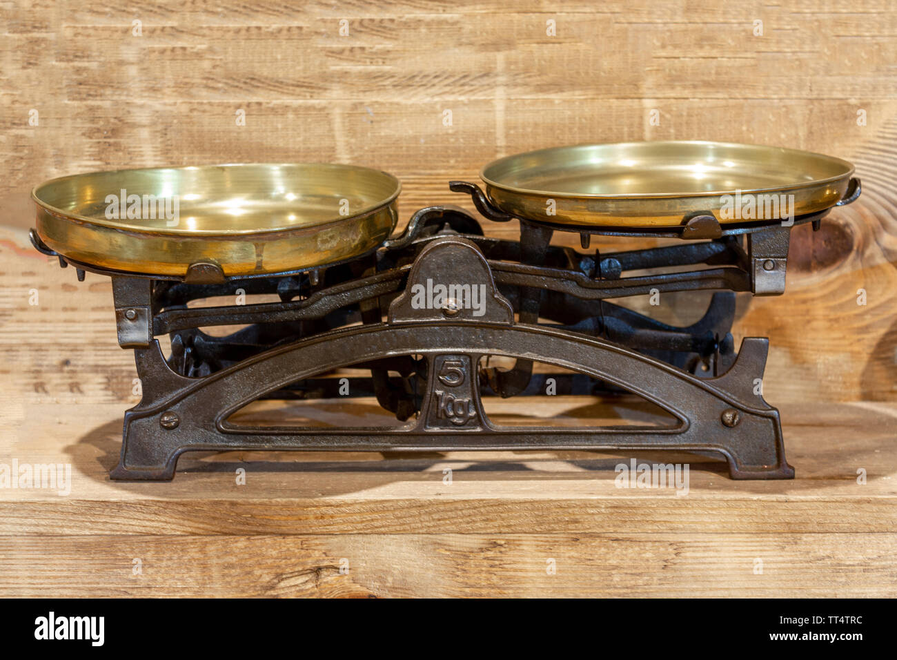 Old antique iron scales on wooden background - Stock Image