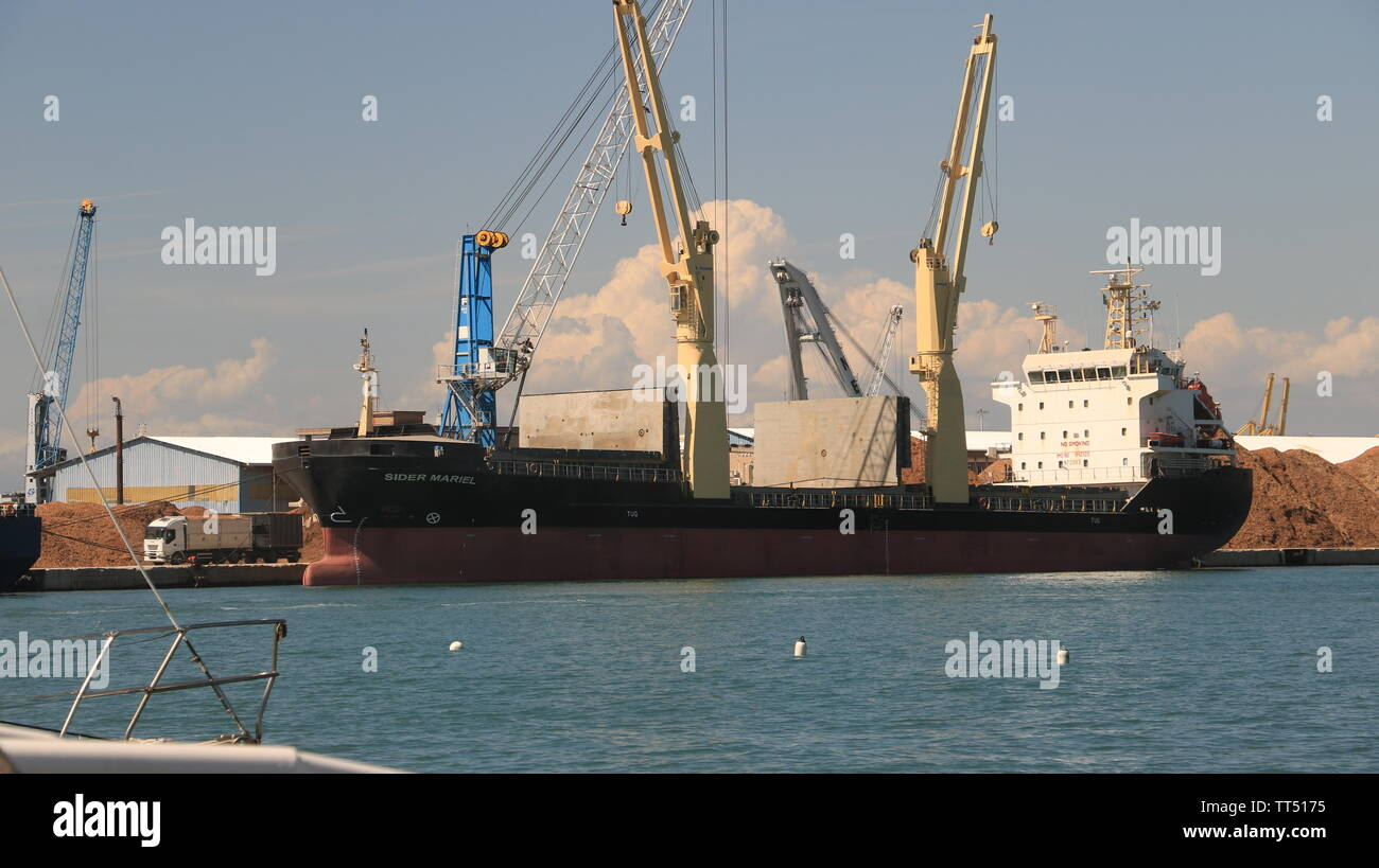 Livorno, Tuscany, Italy. 06/12/2019. Panoramic view of the port. A Cargo ship and a ferry are anchored to the docks. In the foreground numerous sailbo - Stock Image