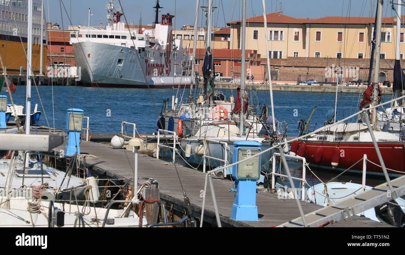 Livorno, Tuscany, Italy. 06/12/2019. Sailboats anchored to the dock of the port.  In the background a large white ship. - Stock Image