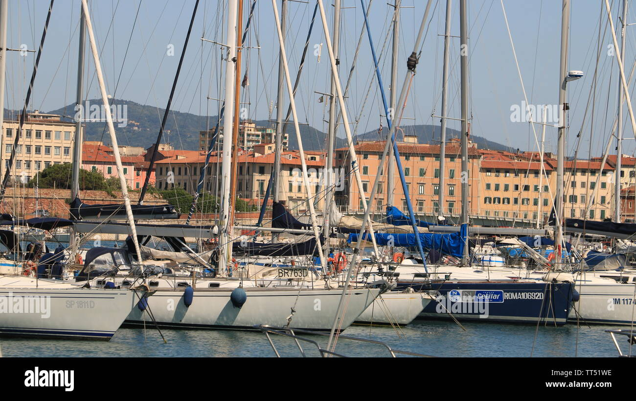 Livorno, Tuscany, Italy. 06/12/2019. Sailboats anchored to the dock of the port. In the background the buildings of the city. - Stock Image
