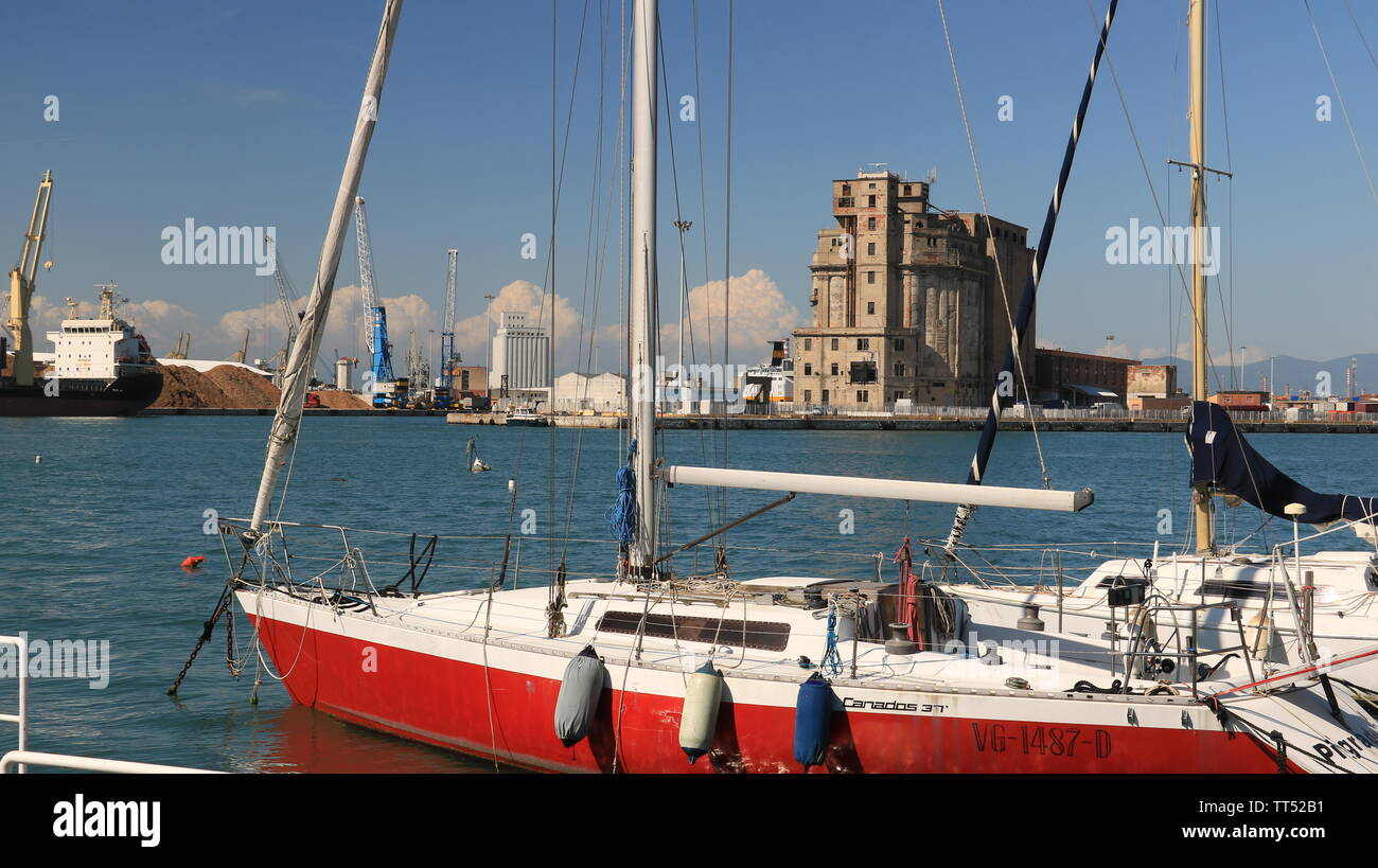 Livorno, Tuscany, Italy. 06/12/2019. Sailboats anchored to the dock of the port. Abandoned warehouses in the background. - Stock Image