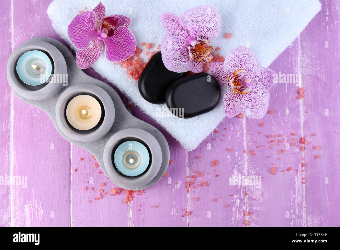 Orchid flowers, spa stones, candles and towel on color wooden background Stock Photo