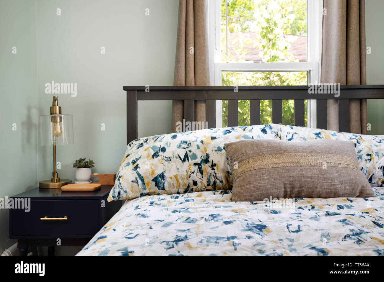 A Comfortable Room With A Bed In Front Of A Window On A Sunny Day And A Nightstand With Some Objects On It Stock Photo Alamy