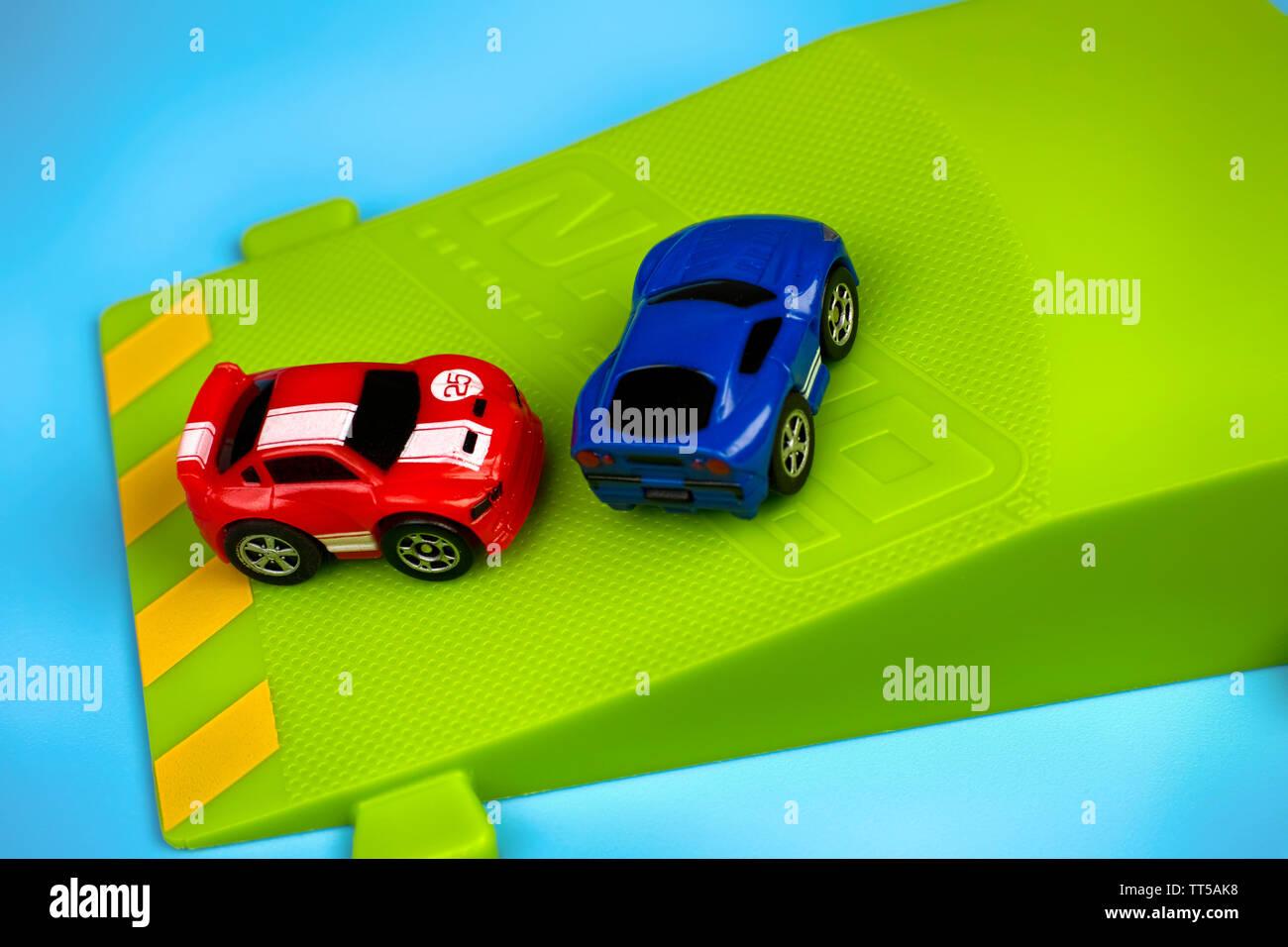 Tambov, Russian Federation - January 25, 2015 Two Nano Speed Micro Cars on green springboard on blue background. Studio shot. - Stock Image