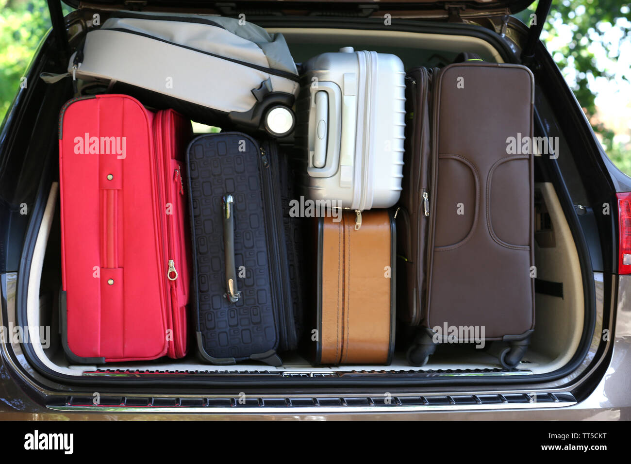 Suitcases and bags in trunk of car ready to depart for holidays - Stock Image