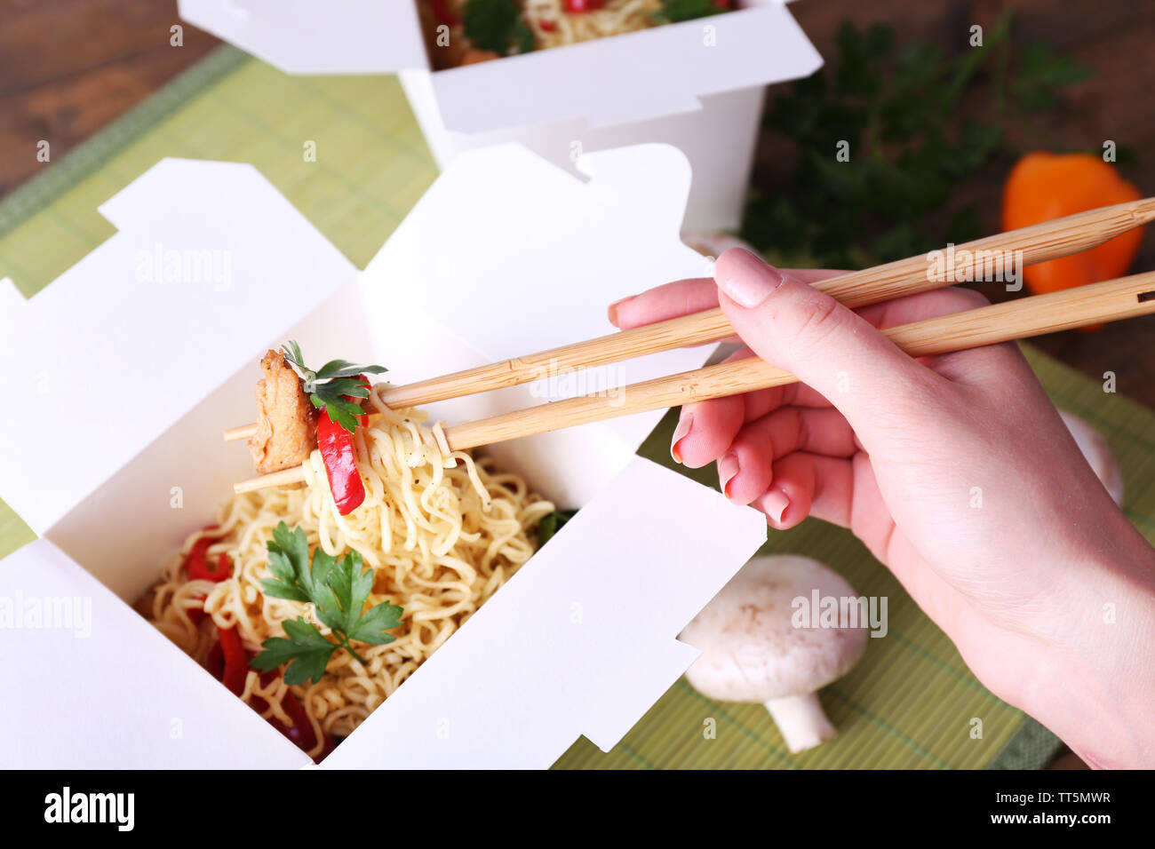 Chinese noodles and sticks in takeaway box on mat background - Stock Image