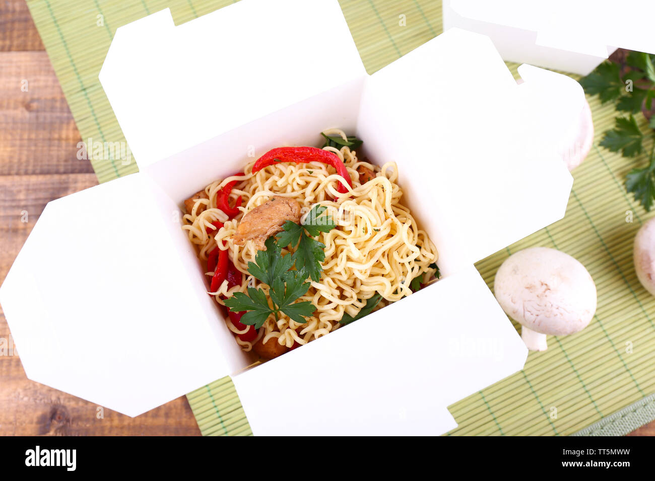 Chinese noodles in takeaway box on mat background - Stock Image