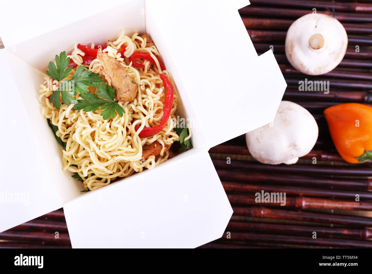 Chinese noodles in takeaway box on bamboo mat background - Stock Image