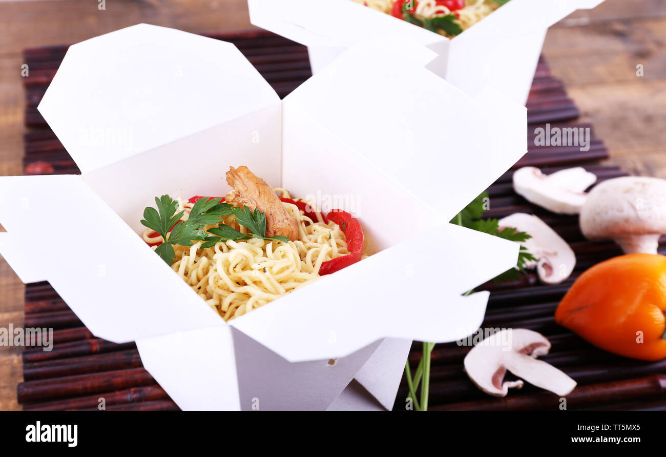 Chinese noodles in takeaway boxes on bamboo mat background - Stock Image