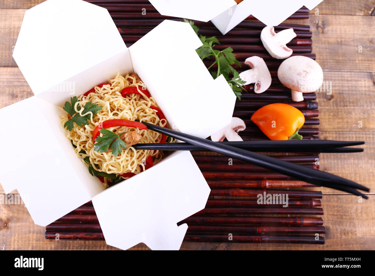 Chinese noodles in takeaway boxes on bamboo mat on wooden background - Stock Image