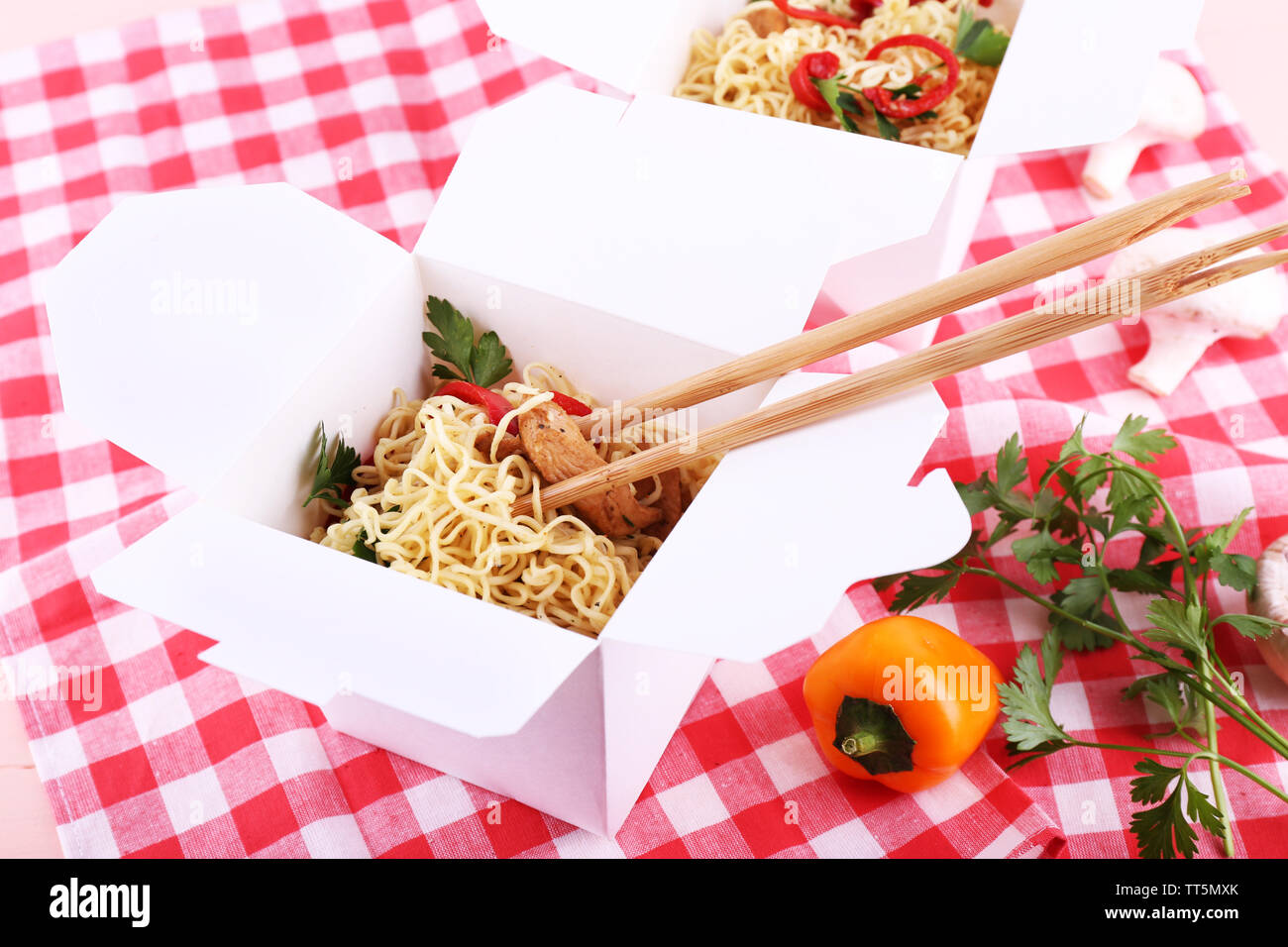 Chinese noodles and sticks in takeaway boxes on fabric background - Stock Image