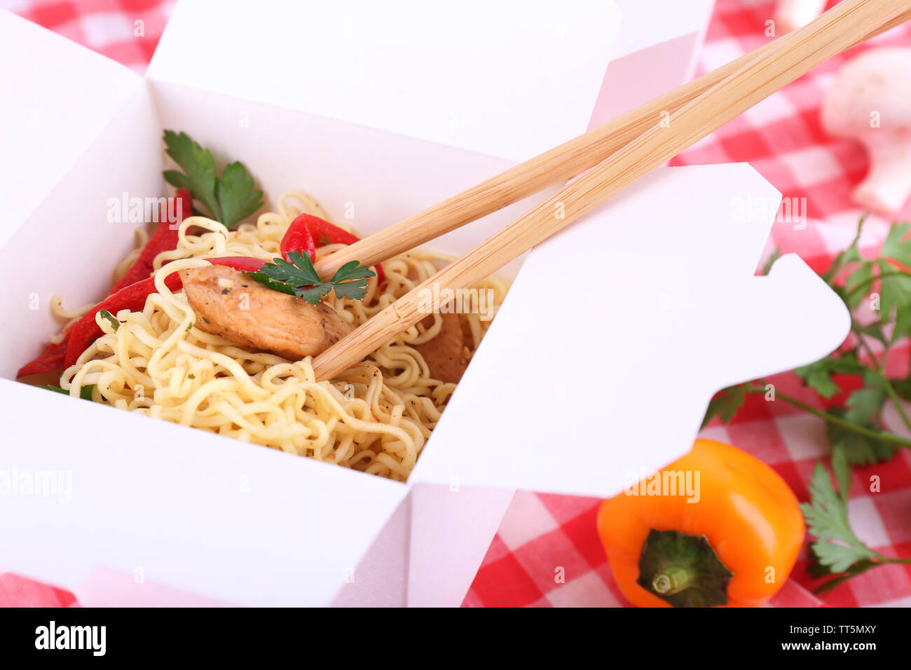 Chinese noodles and sticks in takeaway box on fabric background - Stock Image