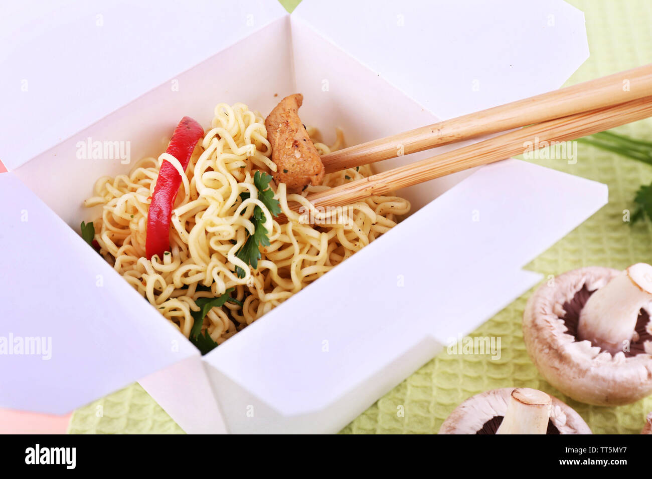 Chinese noodles in takeaway box on fabric background - Stock Image