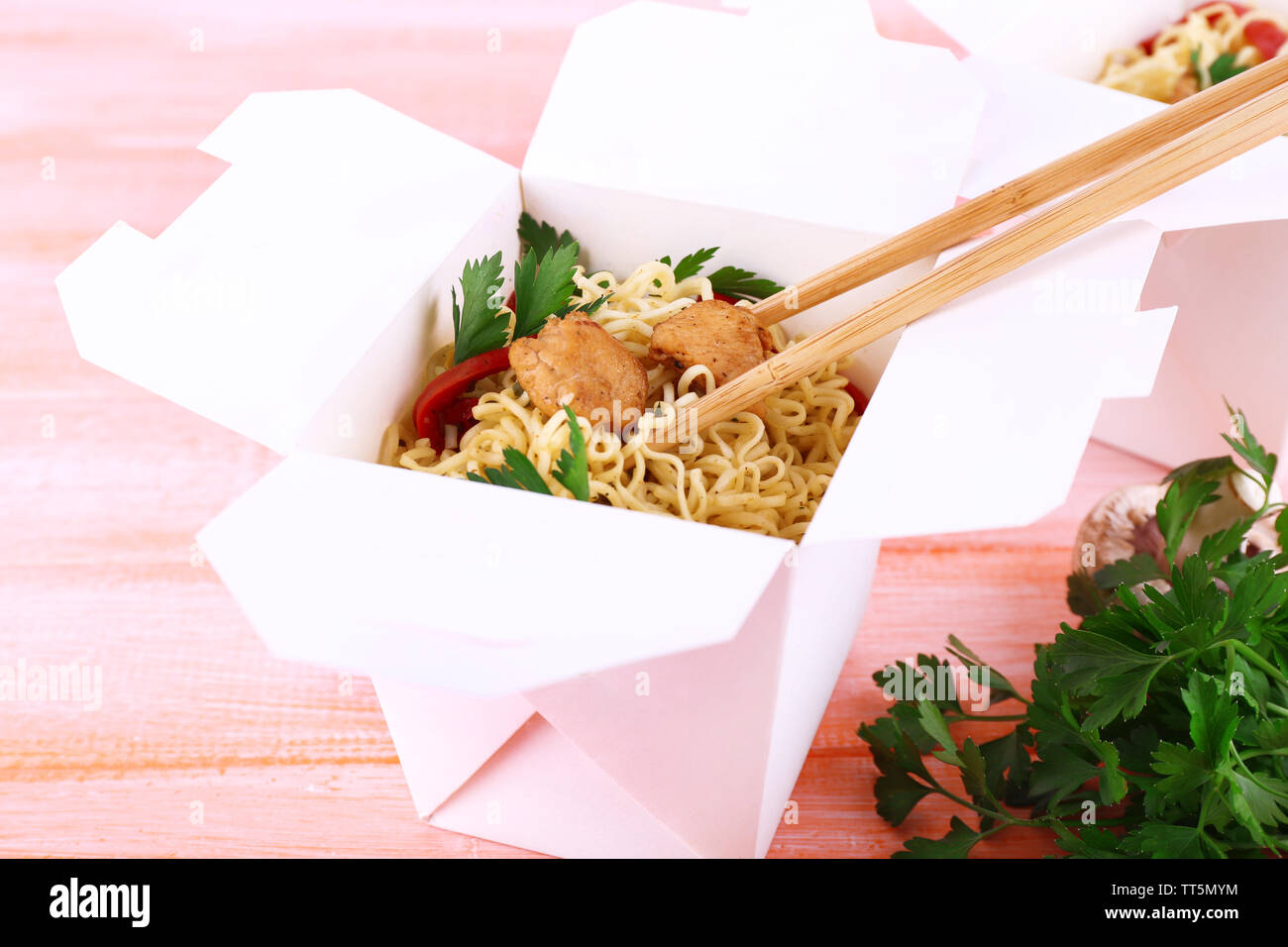 Chinese noodles with meat and pepper in takeaway box on pink background - Stock Image