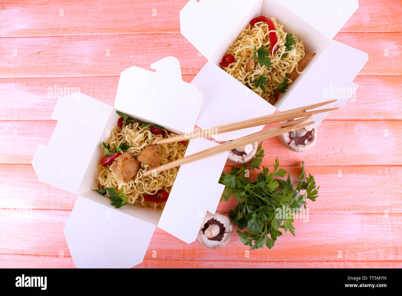 Chinese noodles with meat and pepper in takeaway boxes on pink background - Stock Image