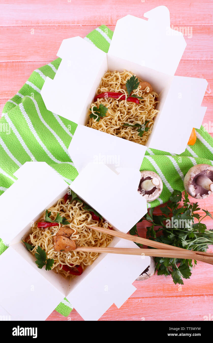 Chinese noodles and sticks in takeaway boxes on green napkin on pink background - Stock Image