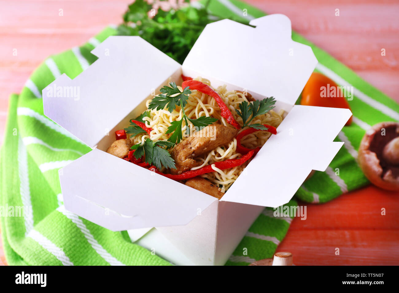 Chinese noodles in takeaway box on green napkin on pink background - Stock Image