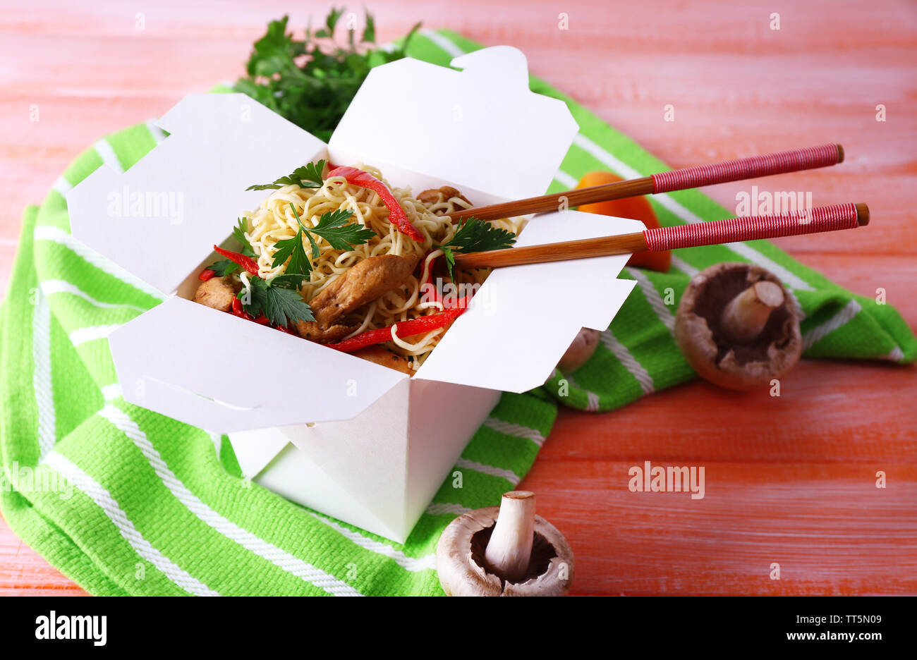 Chinese noodles and sticks in takeaway box on green napkin on pink background - Stock Image