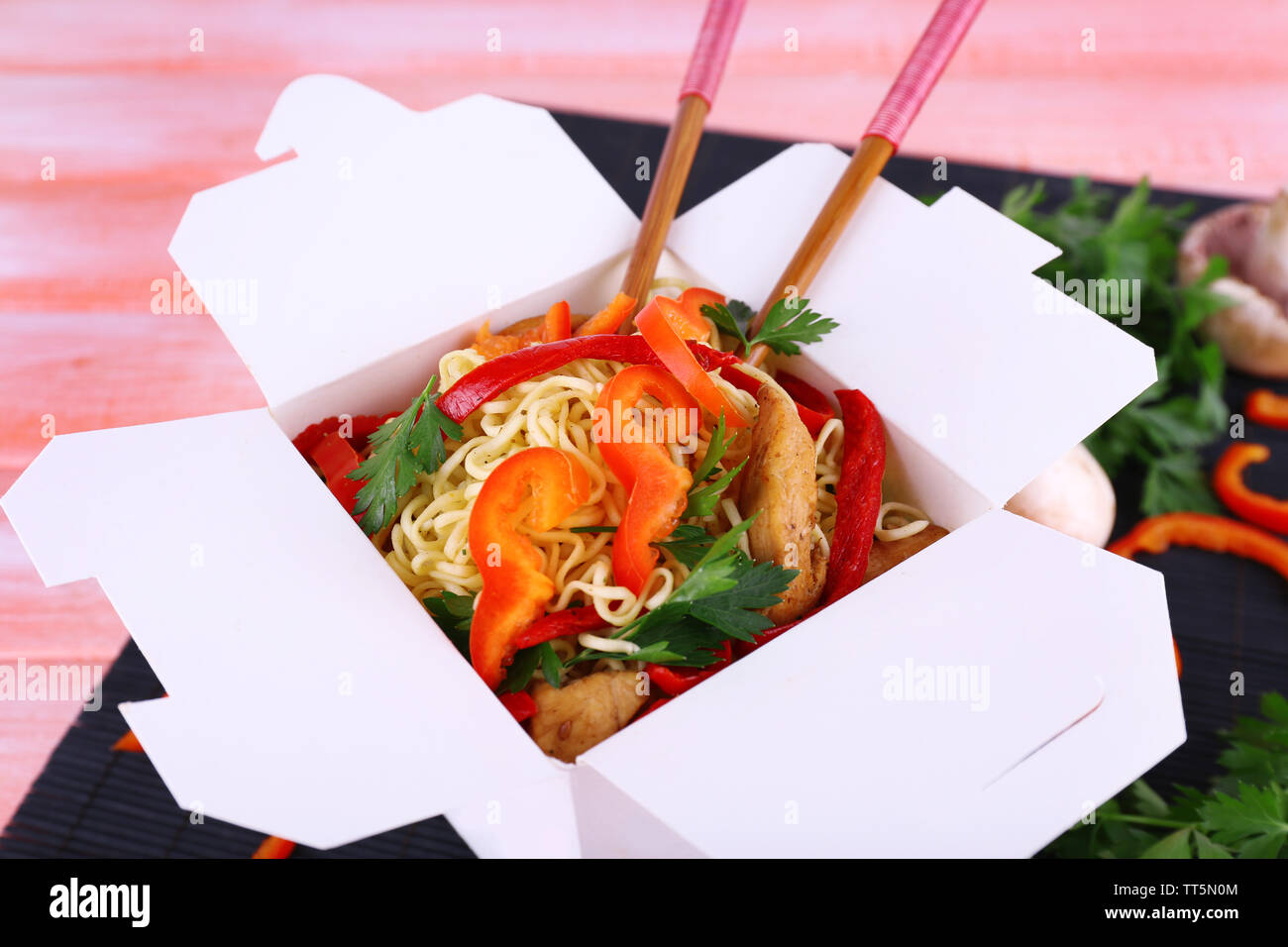 Chinese noodles and sticks in takeaway box on black mat on pink background - Stock Image
