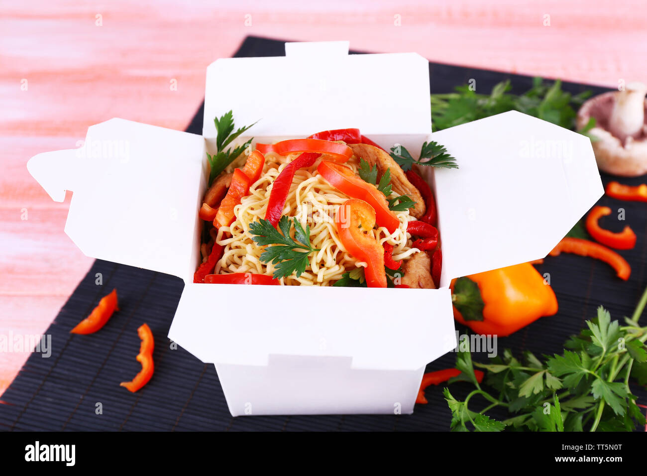 Chinese noodles in takeaway box on black mat on pink background - Stock Image