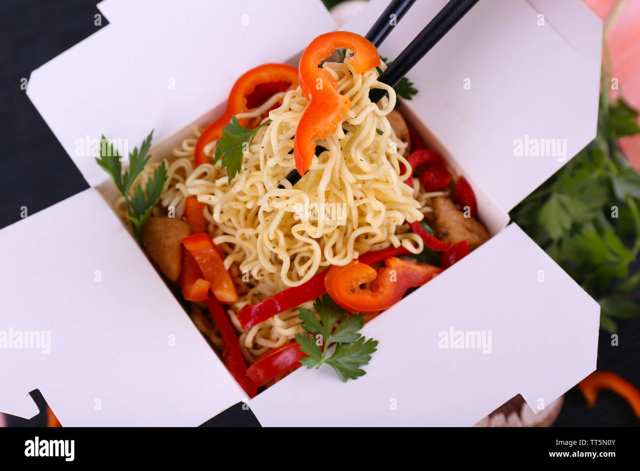 Chinese noodles in takeaway box on black mat background - Stock Image