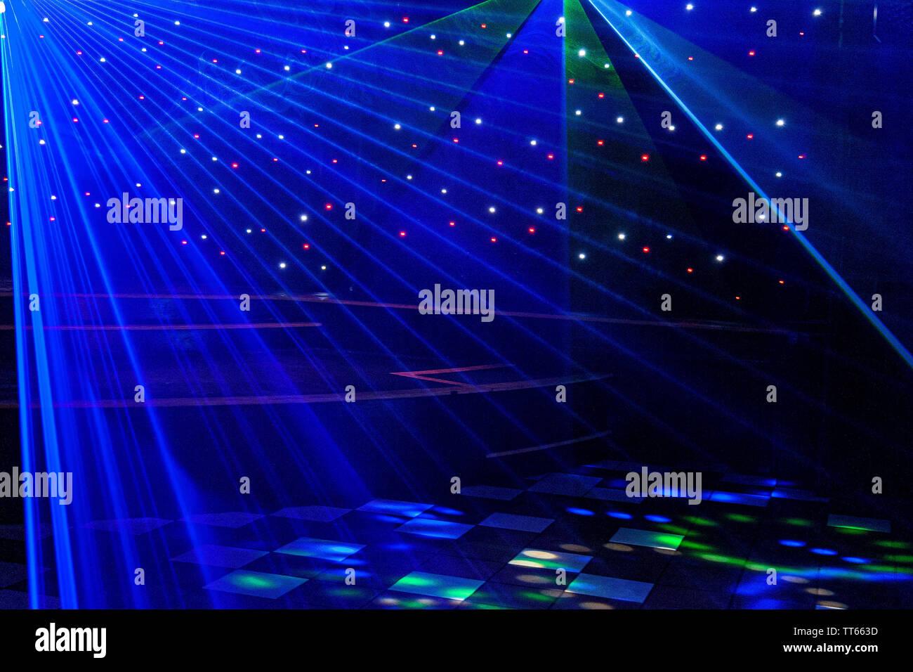 Bright nightclub purple, white, blue laser lights cutting through smoke machine smoke making light and rainbow patterns on the dance floor. Laser ligh - Stock Image