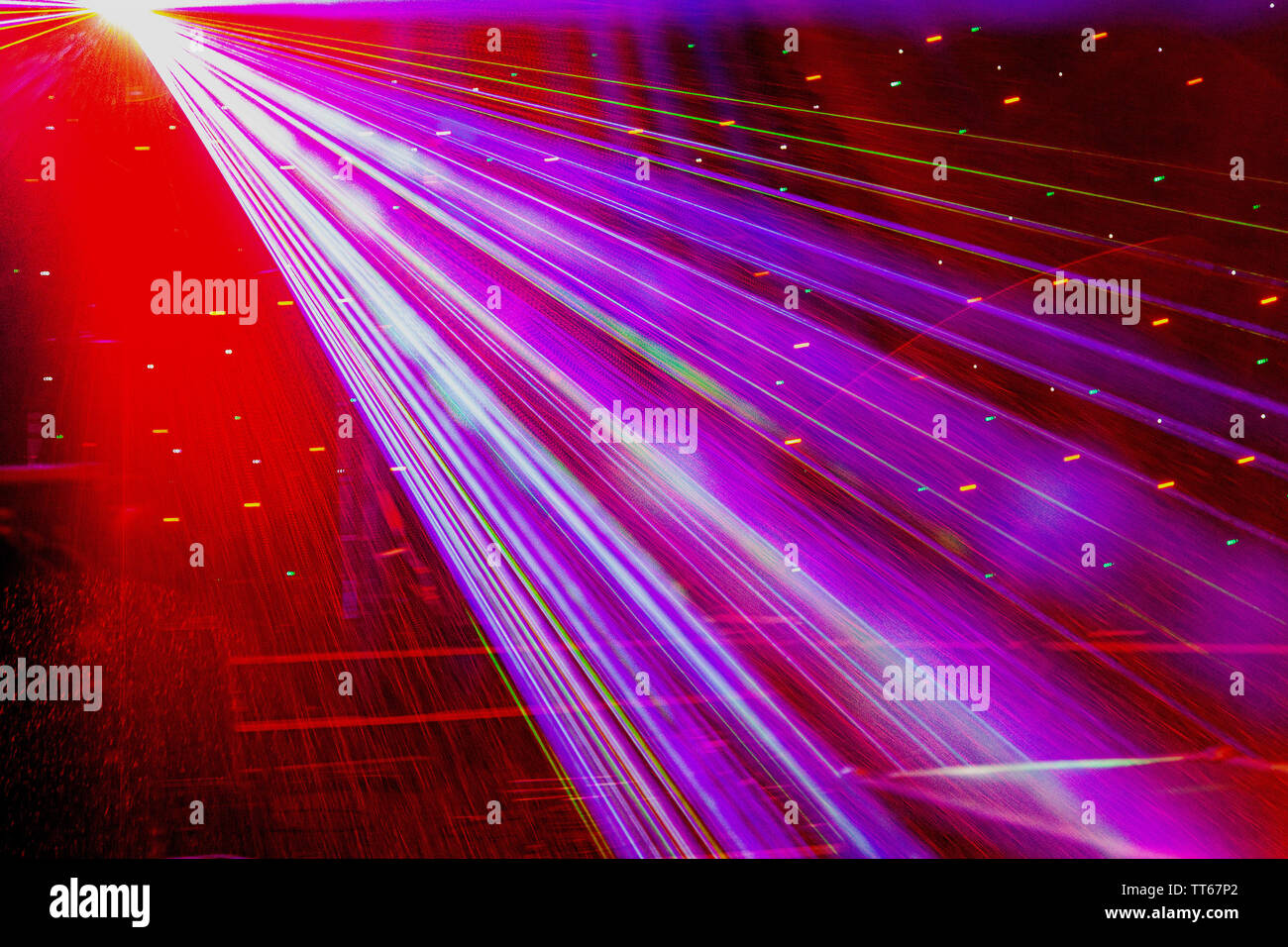 Bright nightclub red laser lights cutting through smoke machine smoke making light and rainbow patterns on the dance floor. Laser lights with bokeh in - Stock Image
