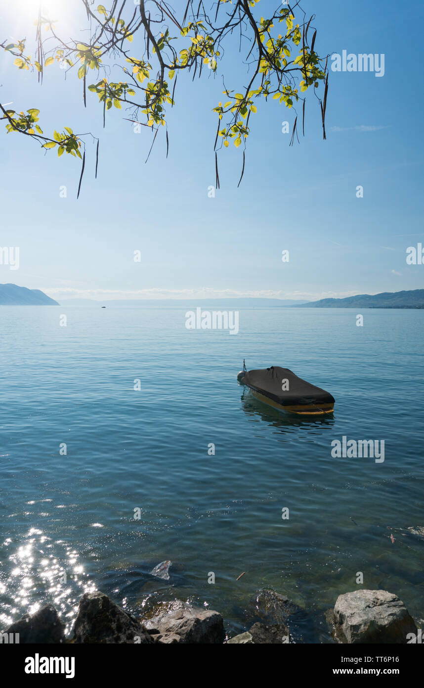 A beautiful view of Lake Geneva and surrounding mountains on a summer day with a single boat in the foreground - Stock Image