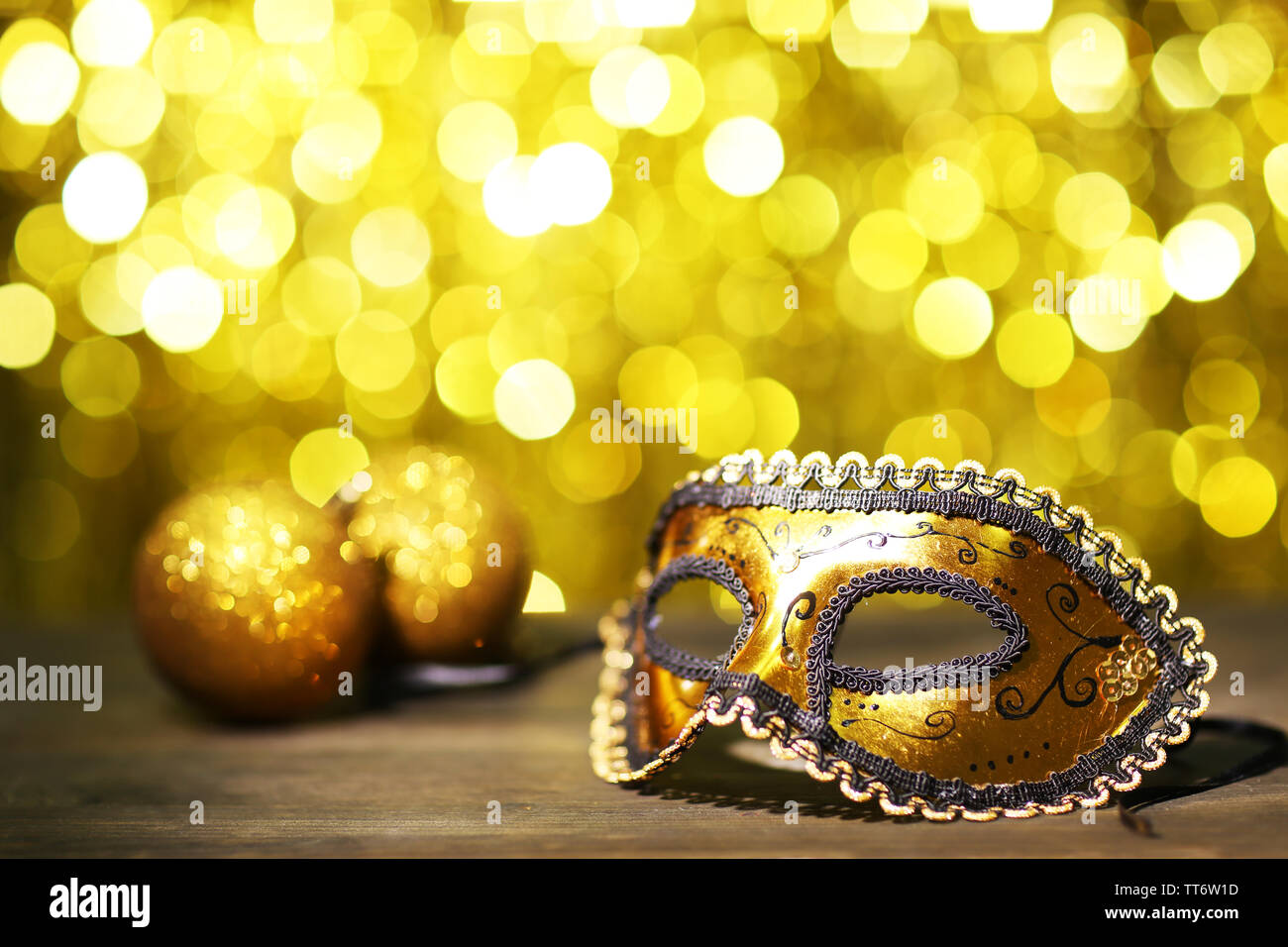 Beautiful carnival mask on table on golden background - Stock Image