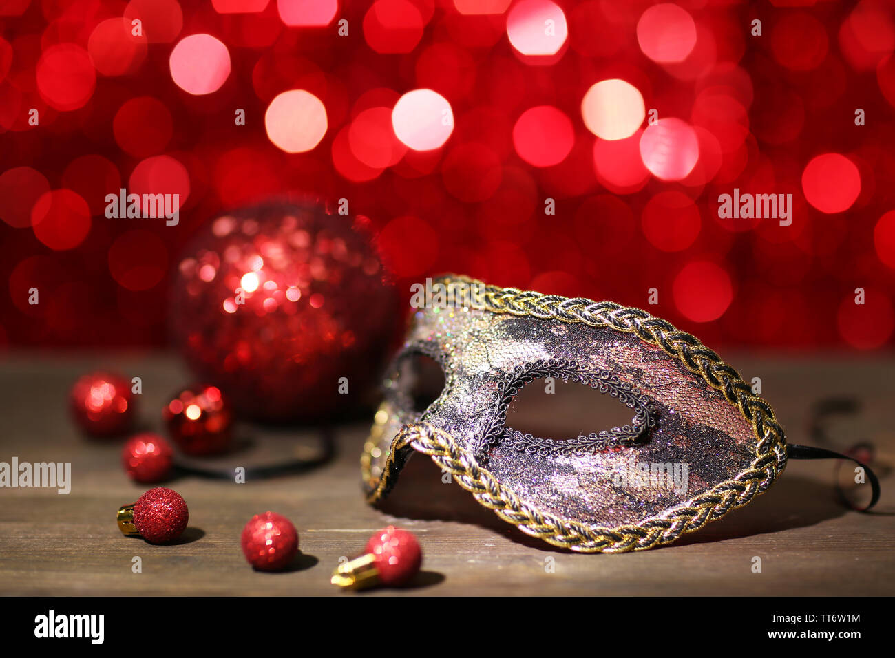 Beautiful carnival mask on table on red background - Stock Image