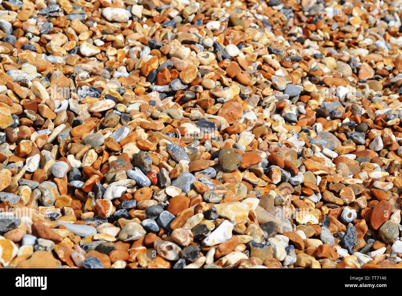 Pebble beach of big oval colorful stones brightly illuminated. Stock Photo