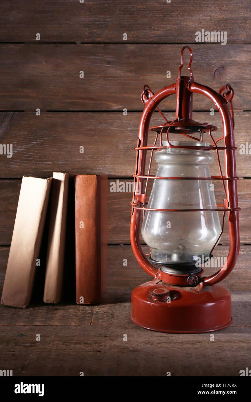 Kerosene lamp with books on rustic wooden background - Stock Image